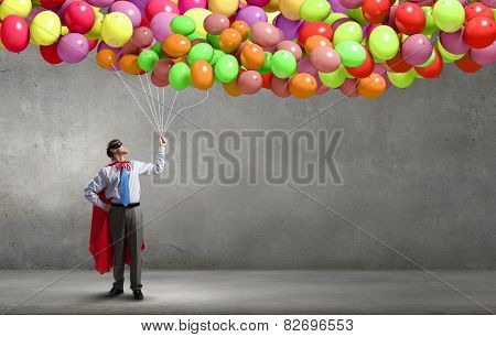 Young confident super guy in mask and cape with bunch of balloons