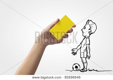 Caricature of football player and human hand showing yellow card