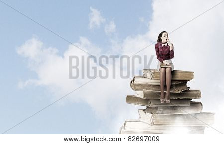 Young woman sitting on pile of books with book in hands