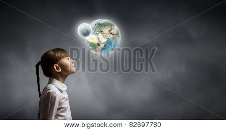 Cute girl of school age looking at Earth planet. Elements of this image are furnished by NASA