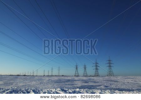 Group of high-voltage electricity power pylons over blue sky and snow covered countryside, Canada