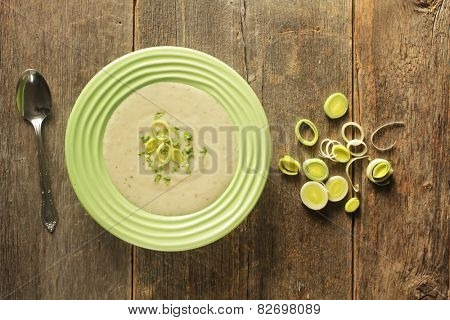 Top view of a bowl of leek soup with fresh leek rings on a wooden background