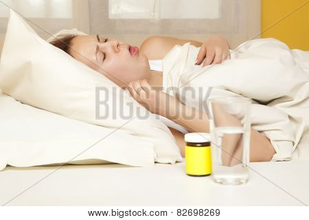 Cough. Female in bed at home caught cold, feeling bad, taking medicines