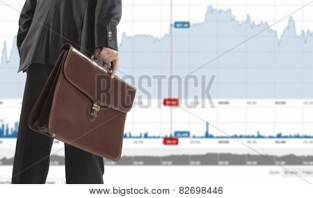 Stock trader with a briefcase looking at monitors