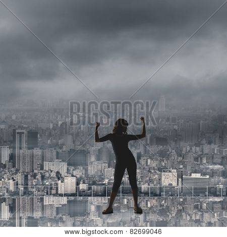 silhouette of Asian woman under heavy clouds in the city. concept of girl power, confident, freedom etc.