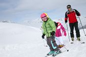 pic of family ski vacation  - Family skiing down ski slope in winter - JPG