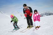 stock photo of playtime  - Ski teacher helping young kids to go down ski slope - JPG