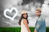 pic of shoulder-blade  - Happy hipster couple holding hands and smiling at camera against green grass under grey sky - JPG