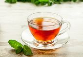 picture of mint leaf  - Cup of tea with mint on leaves wooden table. ** Note: Soft Focus at 100%, best at smaller sizes - JPG