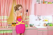 foto of woman glamorous  - Pretty woman doing makeup on her glamorous pink kitchen at home - JPG