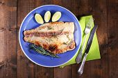 stock photo of pangasius  - Dish of Pangasius fillet with rosemary and lime on wooden table background - JPG