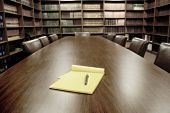 stock photo of book-shelf  - Conference room table with several leather chairs and shelves of books - JPG