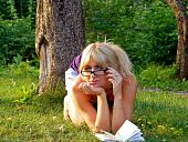 stock photo of swales  - charming young female relaxing in urban park on a summer day - JPG