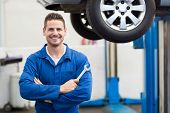 picture of garage  - Mechanic smiling at the camera holding tool at the repair garage - JPG