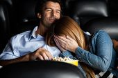 image of watching movie  - Frightened mid adult woman leaning on man while watching movie in cinema theater - JPG