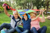 image of grandparent child  - Portrait of happy boy with grandparents holding kite over heads at campsite - JPG