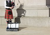stock photo of bagpiper  - a scottish man in a kilt  playing the bagpipes - JPG