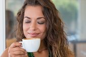 stock photo of  eyes  - Close Up Of A Woman Taking In Smell Of Coffee With Eyes Closed - JPG