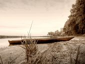 stock photo of derelict  - Sepia retro style picture of derelict boathouse and rowing boats landscape - JPG
