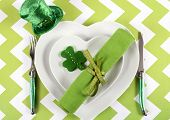 stock photo of leprechaun hat  - Happy St Patricks Day table place setting with heart shape plates shamrock cookie and leprechaun hat on green and white chevron stripe table - JPG