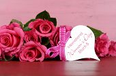 stock photo of bunch roses  - International Womens Day March 8 pink roses with gift tag message on vintage pink wood background - JPG