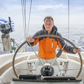 pic of early-man  - Young man Skipper early in the morning at the helm of a yacht in the open sea - JPG