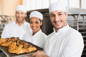 stock photo of trays  - Team of bakers smiling at camera with trays of croissants in the kitchen of the bakery - JPG