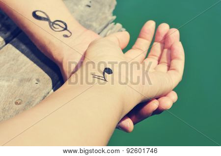 closeup of a young caucasian man with some musical symbols tattooed in his wrists, chilling out on a wooden pier at the sea