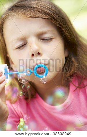 Head And Shoulders Portrait Of Girl Blowing Bubbles