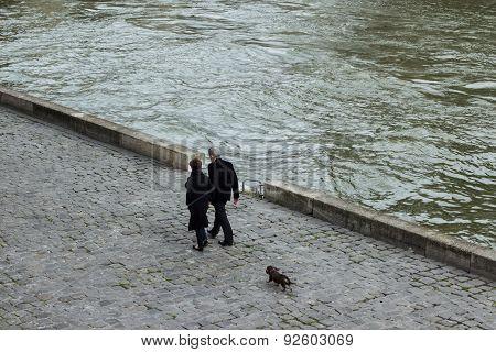 Couple walk their dog along river Seine, Paris