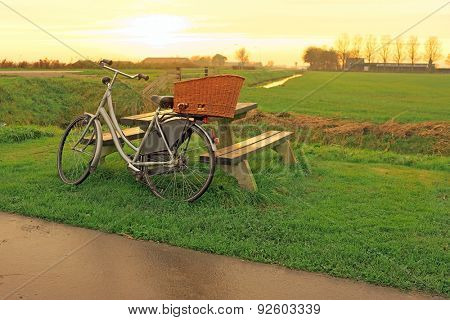 Bike against a picnic bench in the countryside from the Netherlands at twilight