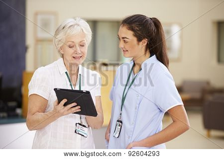 Female Consultant In Meeting With Nurse Using Digital Tablet