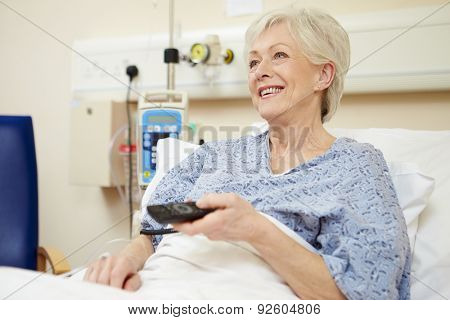 Senior Female Patient Watching TV In Hospital Bed