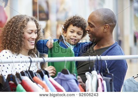 Family Looking At Clothes On Rail In Shopping Mall