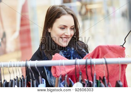 Woman Looking At Clothes On Rail In Shopping Mall