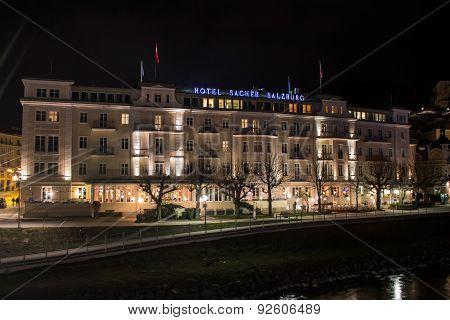 Salzburg, Austria - March 11, 2015: Illuminated Hotel Sacher on the river Salzach close to the Makartsteg