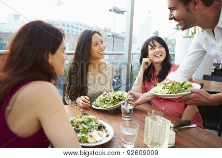 Three Female Friends Enjoying Lunch At Rooftop Restaurant