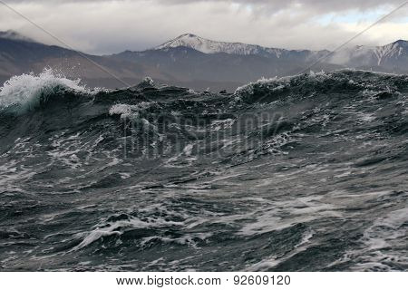 high storm wave on the background of the North shore in bad weather