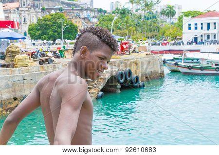 BAHIA, BRAZIL - CIRCA NOVEMBER 2014: Boy preparing to jump into the water in Salvador, Brazil.