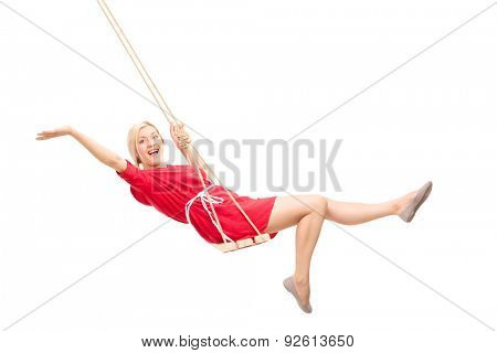 Joyful woman swinging on a swing and gesturing with her hands isolated on white background