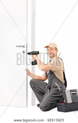 Vertical shot of a young locksmith screwing a lock on a door with a hand drill and looking at the camera isolated on white background