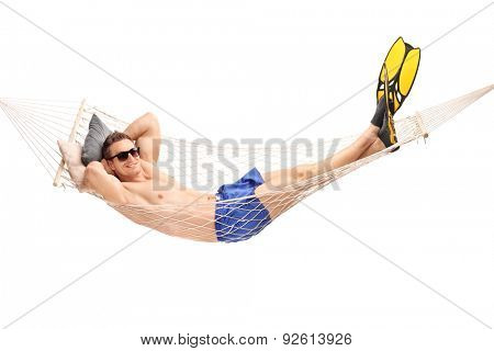 Shirtless young guy with diving flippers lying in a hammock and looking at the camera isolated on white background