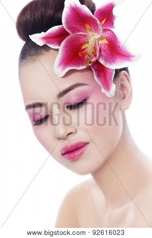 Portrait of young beautiful healthy asian girl with radiant skin and pink lily in her hair over white background