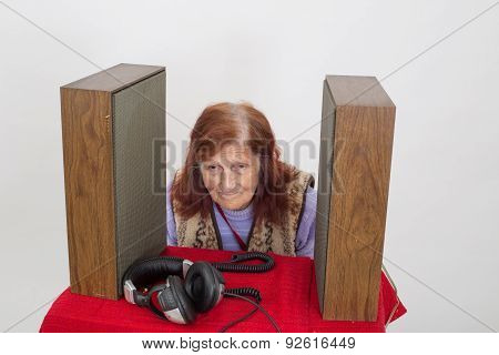 Elderly Lady Listening Attentively To The Old Radio .