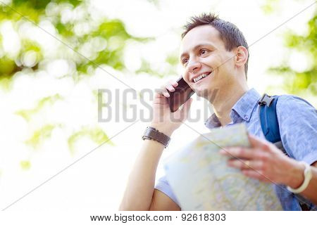 Man holding map outdoors and talking by phone