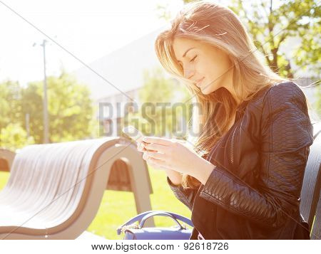 Young woman typing sms message. Natural sunflare