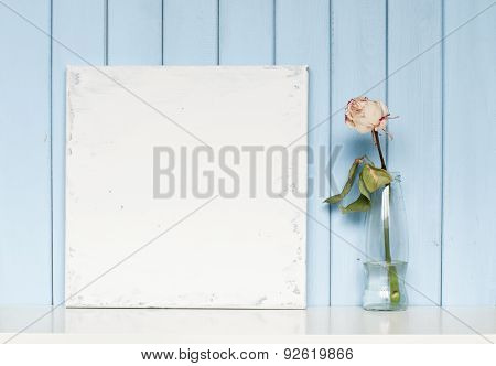 A Blank Canvas And White Rose In The Bottle