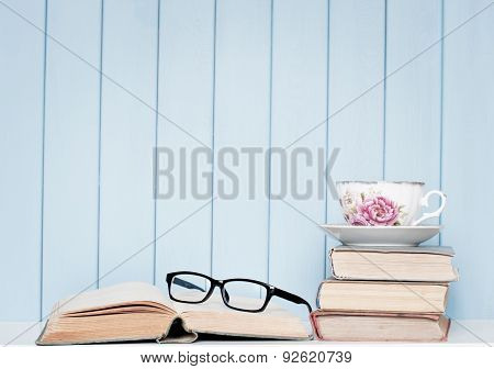 Old Antiquarian Books, Glasses And China Cup On The Bookshelf