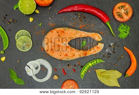 Salmon Fish And Spices On Black Stone.
