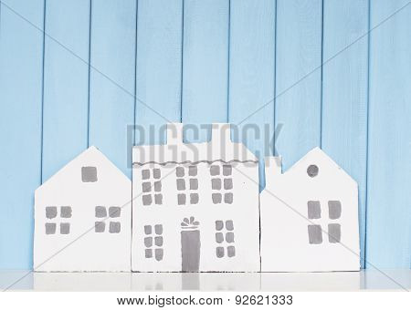 Three Wooden Houses On The Bookshelf